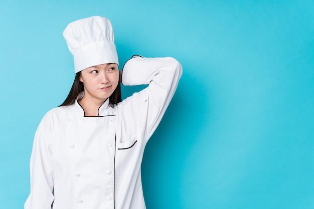 Молодая китайская женщина шеф-повара изолировала трогательный затылок, думая и делая выбор.