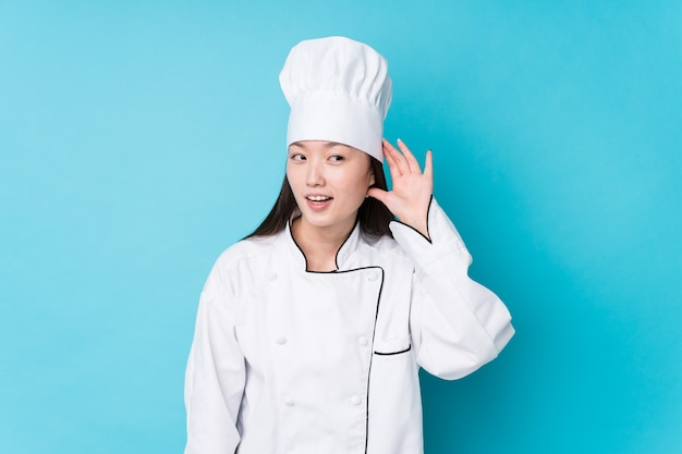 Young chinese chef woman isolated trying to listening a gossip.