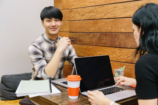 Young chinese college student preparing exams with a female colleage