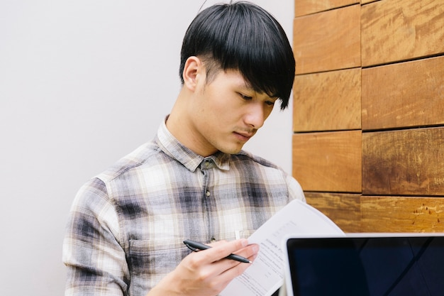 Young chinese college student preparing exams with his laptop