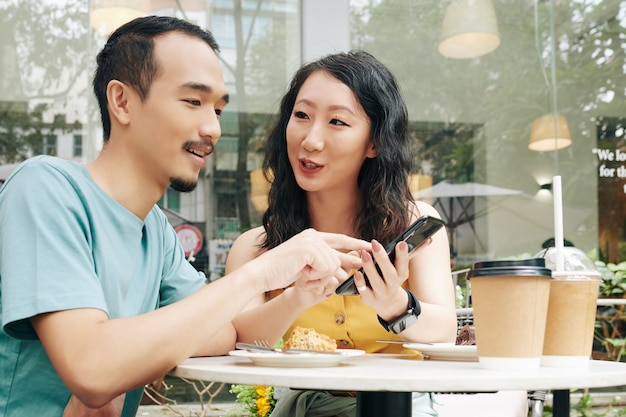 Young chinese couple discussing posts or photos on social media when enjoying romantic date in outdoor cafe