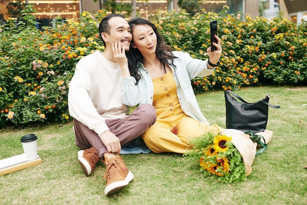 Young chinese couple spending romantic date in city park and taking selfie on smartphone for social media