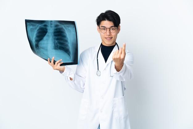 来たるジェスチャーをしている白で隔離されたレントゲン写真を保持している若い中国人医師の男