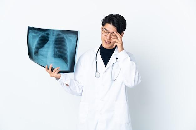 白笑いで分離されたレントゲン写真を保持している若い中国人医師の男