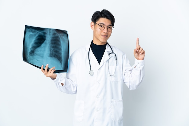 Young chinese doctor man holding radiography isolated on white wall showing and lifting a finger in sign of the best