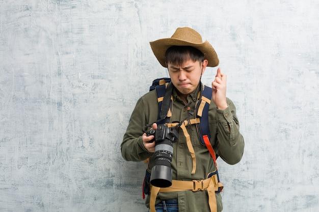 행운을 위해 카메라 횡단 손가락을 들고 젊은 중국 탐험가 남자