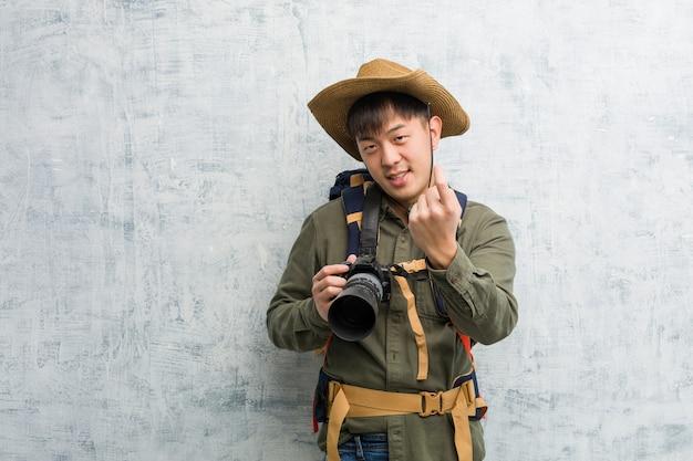 Молодой китайский исследователь мужчина держит камеру, приглашая приехать