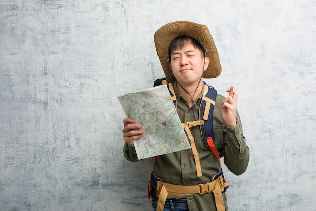 행운을 갖는 손가락을 횡단하는지도를 들고 젊은 중국 탐험가 남자