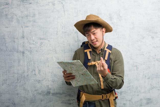 来て招待する地図を保持している若い中国人探検家男