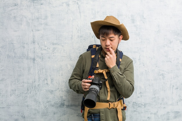 Young chinese explorer man holding a camera relaxed thinking about something  at a