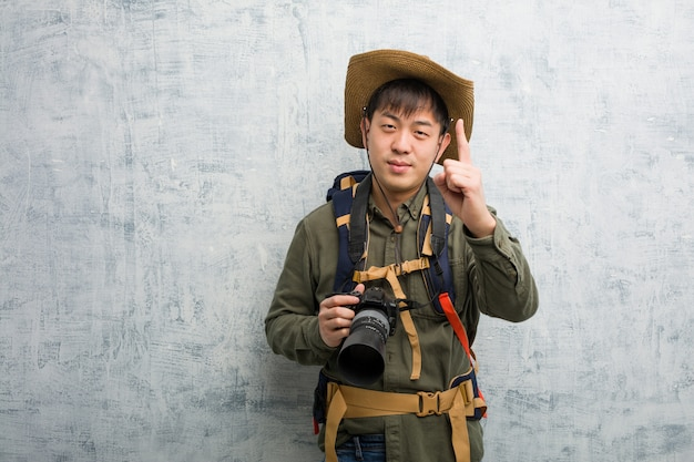 Young chinese explorer man holding a camera showing number one