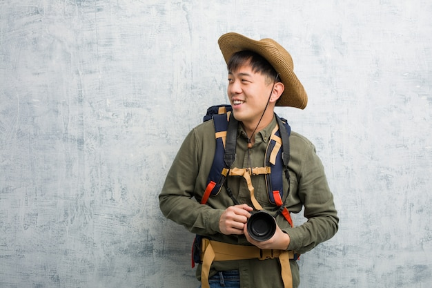 Young chinese explorer man holding a camera smiling confident and crossing arms, looking up
