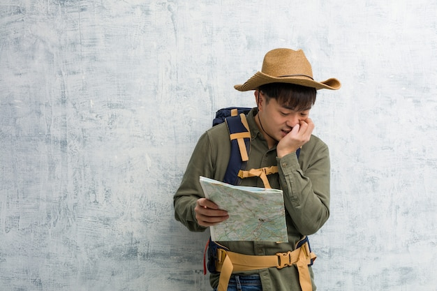 Young chinese explorer man holding a map biting nails, nervous and very anxious