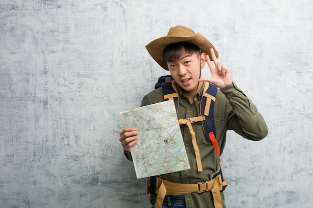 Young chinese explorer man holding a map fun and happy doing a gesture of victory