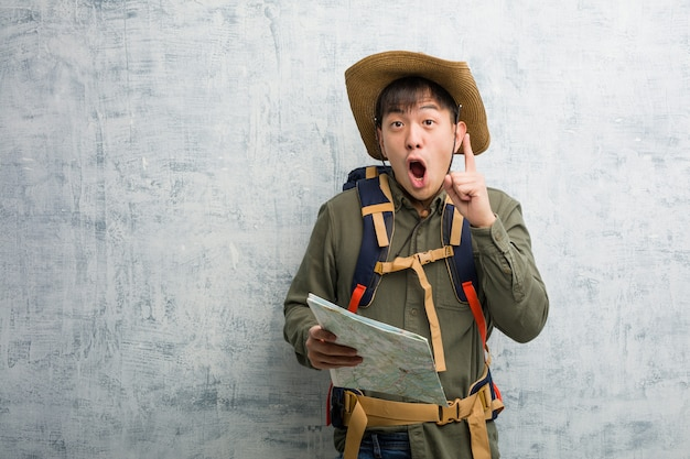 Young chinese explorer man holding a map having a great idea, concept of creativity