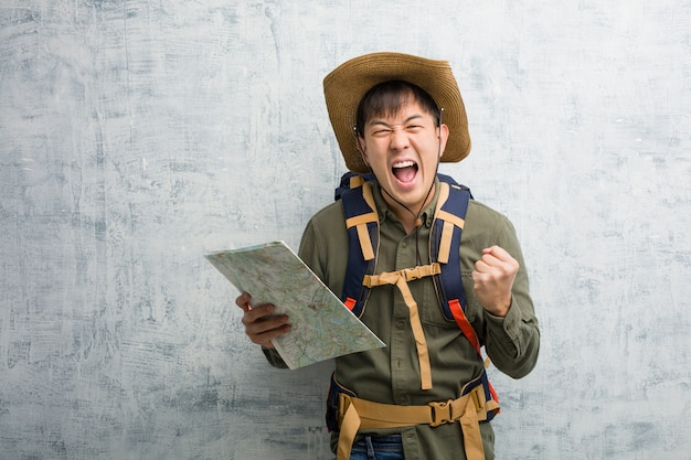 Young chinese explorer man holding a map surprised and shocked