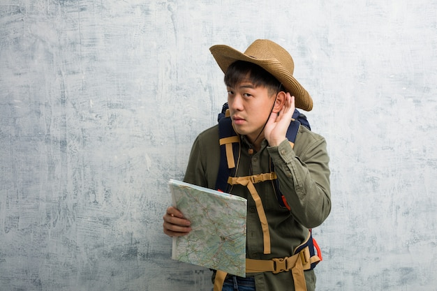Young chinese explorer man holding a map try to listening a gossip