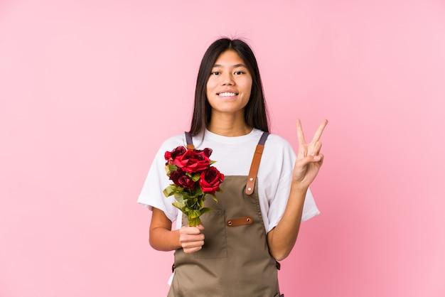 Молодой китайский садовник женщина, держащая изолированные розы, показывая номер два пальцами.