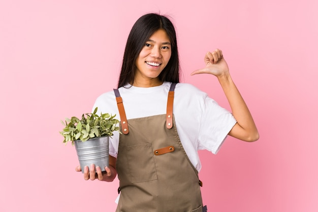 Young chinese gardener woman holding a plant isolated feels proud and self confident, example to follow.