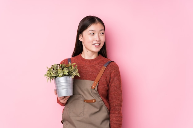 Young chinese gardener woman holding a plant isolated looks aside smiling, cheerful and pleasant.