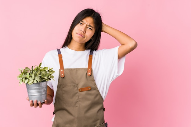 Young chinese gardener woman holding a plant isolated touching back of head, thinking and making a choice.