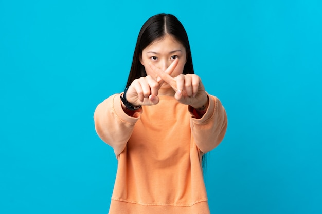 Young chinese girl over blue wall making stop gesture with her hand to stop an act