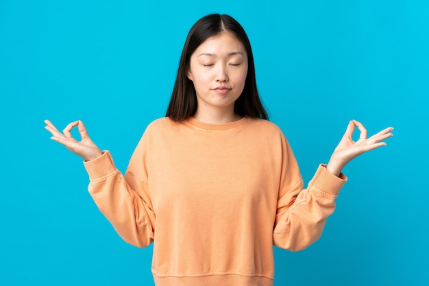 Young chinese girl over blue in zen pose