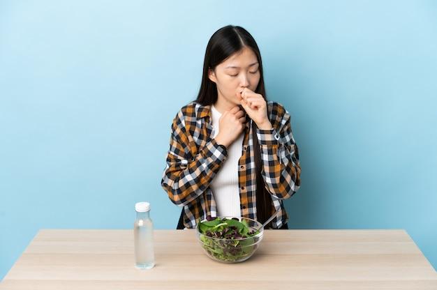 Молодая китайская девушка ест салат много кашель