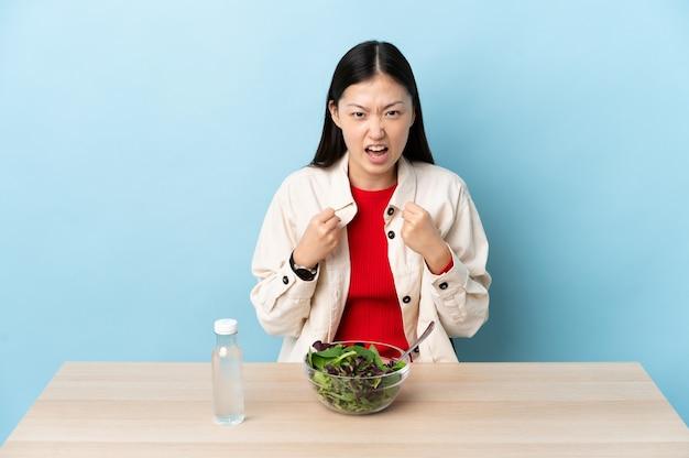 悪い状況に不満を持ってサラダを食べる中国の少女