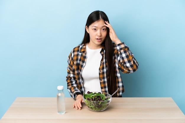샐러드를 먹는 어린 중국 소녀는 무언가를 실현하고 해결책을 의도했습니다.