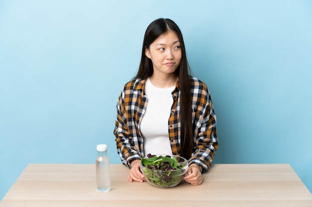 Молодая китайская девушка ест салат, имея сомнения, глядя вверх