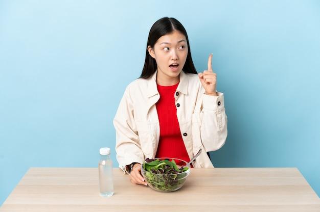 샐러드를 먹는 어린 중국 소녀는 손가락을 들어 올리면서 해결책을 실현하려고합니다.