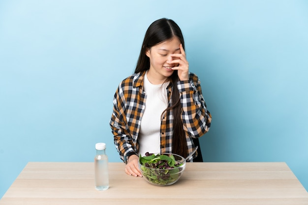 笑ってサラダを食べる中国の少女