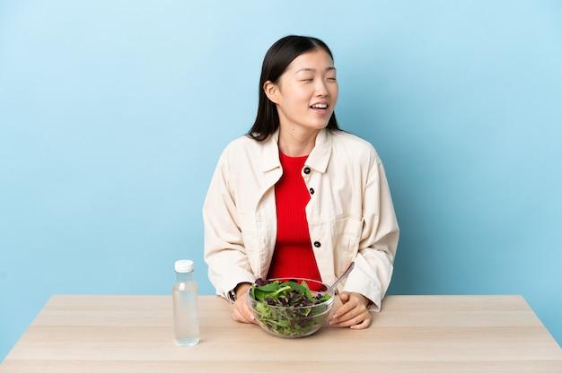 Молодая китайская девушка ест салат смеясь