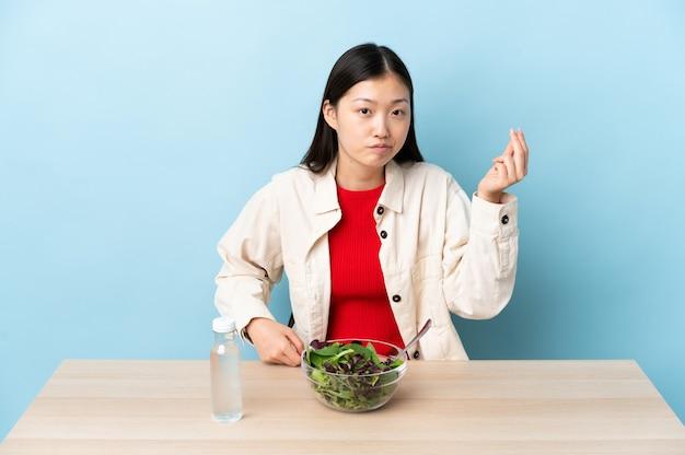 이탈리아 제스처를 만드는 샐러드를 먹는 중국 소녀