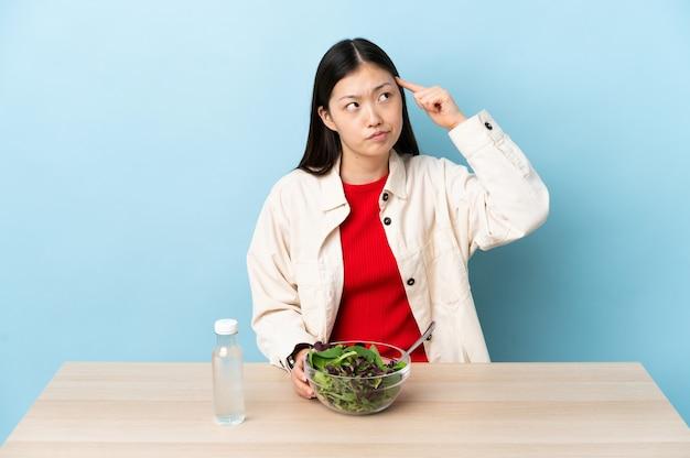 Молодая китаянка ест салат, делая жест безумия, положив палец на голову