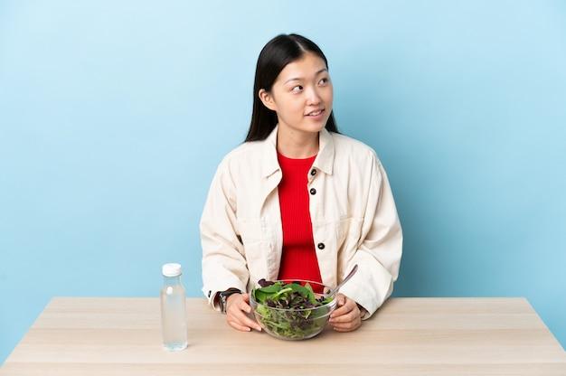 찾는 동안 아이디어를 생각하는 샐러드를 먹는 어린 중국 소녀