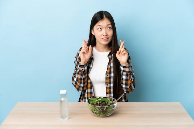 指を交差させてサラダを食べて、最高を願って若い中国の女の子