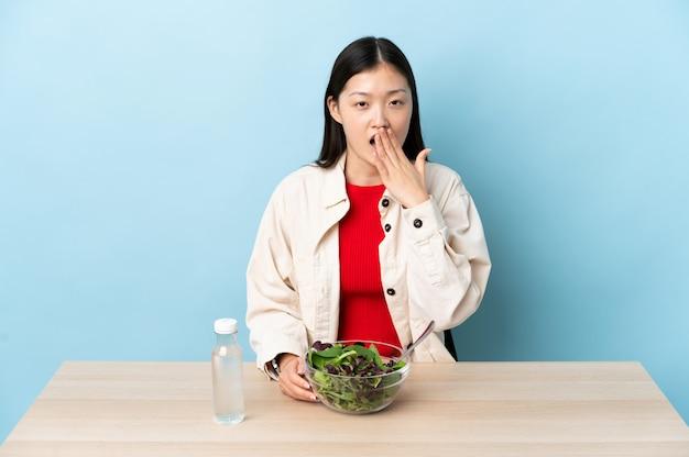 젊은 중국 여자는 하품 샐러드를 먹고 손으로 활짝 열려 입을 덮고