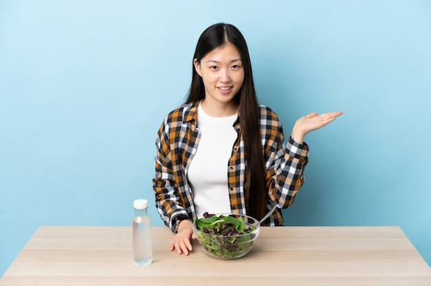 Young chinese girl eating a salad holding copyspace imaginary on the palm to insert an ad