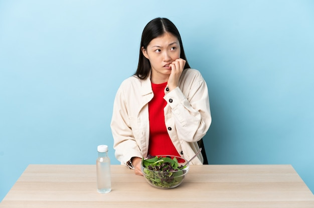 Young chinese girl eating a salad is a little bit nervous