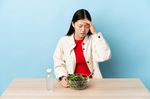 Young chinese girl eating a salad with headache