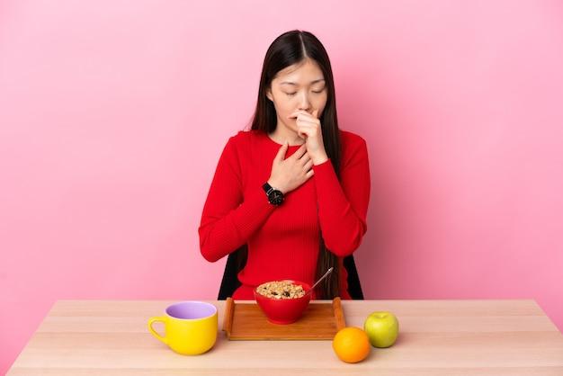 Молодая китайская девушка завтракает за столом и много кашляет