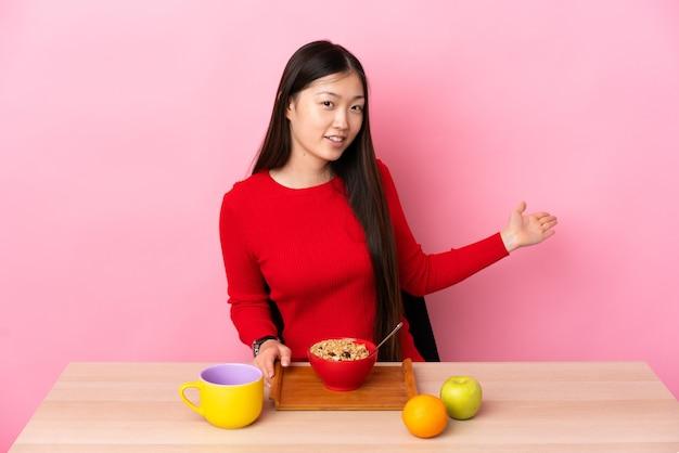 来るように誘うために手を横に伸ばしてテーブルで朝食をとっている若い中国人の女の子
