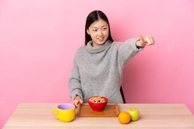 제스처를 엄지 손가락을주는 테이블에서 아침을 먹고 젊은 중국 소녀