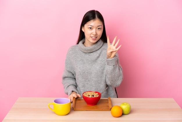 젊은 중국 소녀 행복 테이블에서 아침을 먹고 손가락으로 세 세