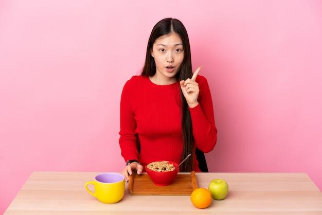 손가락을 들어 올리는 동안 솔루션을 실현하려는 테이블에서 아침을 먹고 젊은 중국 여자