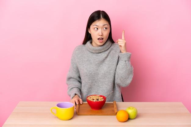 손가락을 들어 올리는 동안 해결책을 실현하려는 테이블에서 아침 식사를하는 젊은 중국 소녀