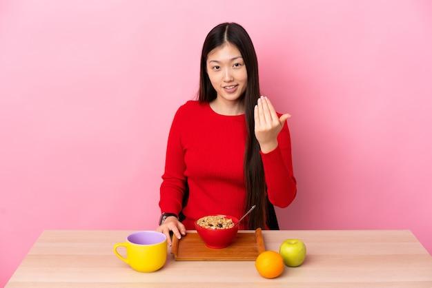 손으로와 서 초대 테이블에서 아침을 먹고 젊은 중국 소녀. 와줘서 행복해