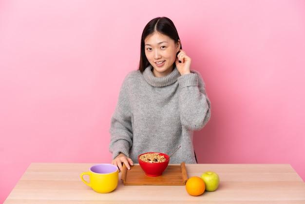 笑ってテーブルで朝食を食べている若い中国の女の子